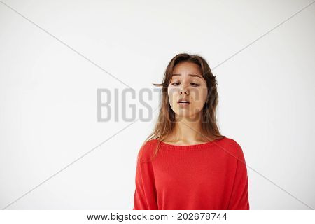 Studio portrait of funny goofy young Latin brunette woman having fun indoors fooling around making faces and squinting eyes trying to see tip of her nose. People leisure fun and relaxation