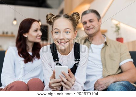 mature parents and teen girl with smartphone in cafe