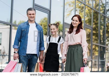 beautiful happy family walking with shooping bags