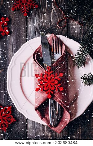 Christmas table setting. Pink plate knife and fork. Christmas Decorations - red snowflakes fir branch on wooden background table.