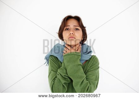 Beautoful young latin female cuddling in warm scarf and holding hands on her neck having sore throat and cough her eyes full of pain. Infection virus flu cold sickness and unwellness concept