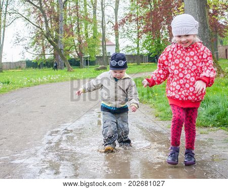 Children siblings are playing in puddle without gumboots. Kids are very happy with the game and enjoy it. The puddle is in a park.