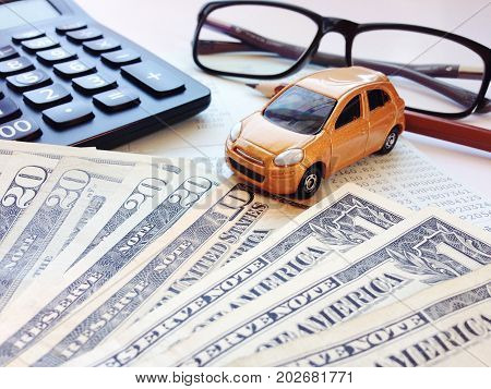 Business, finance, saving money, banking or car loan concept : Miniature car model, calculator, dollar money, eyeglasses, pencil and saving account book or financial statement on office desk table