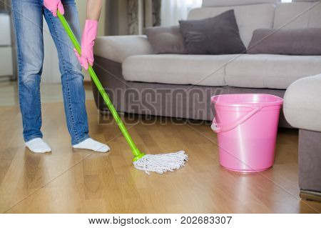 young woman in protective pink gloves using a wet-mop while cleaning floor in  house