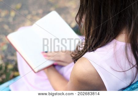 Student girl reading book. A woman with an open book lying on her lap on a Park bench.