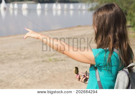 Woman traveller with compass in hand points by finger right direction. Travel concept.
