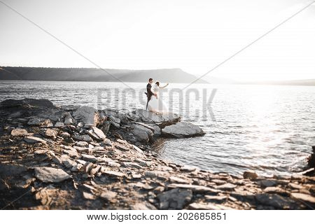 Happy wedding couple staying over beautiful landscape.
