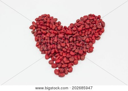 A heart made by little red stones put one next to the other on a white surface.