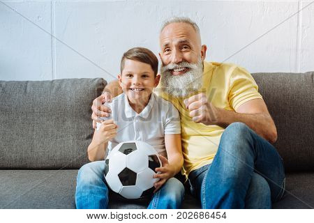 Exciting game. Upbeat senior man sitting on the couch next to his grandson with a ball in the lap and watching an important football game, looking excited