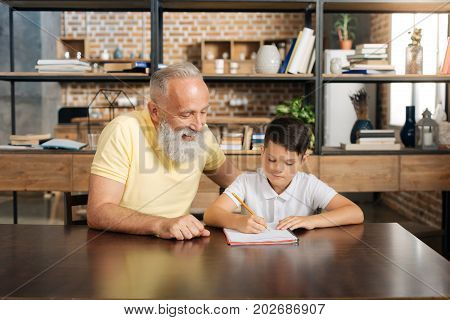 Together easier. Cheerful elderly man sitting at the table next to his pre-teen grandson and helping him with school home assignment