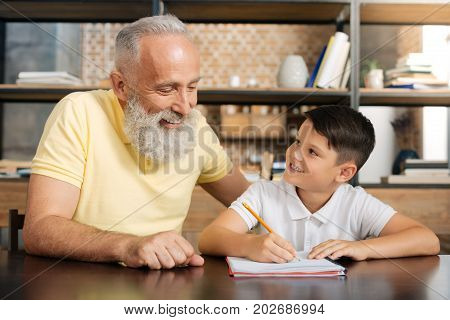 Caring grandfather. Joyful senior man sitting next to his beloved little grandson and helping him do math home assignment