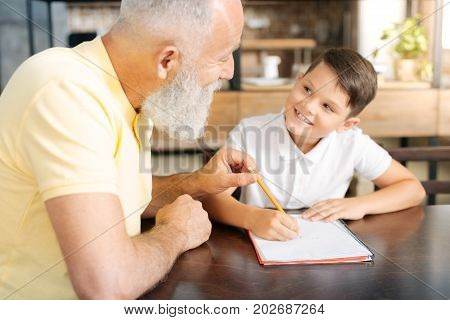 Helpful grandparent. Upbeat pleasant senior man holding the tip of his grandsons pencil and giving him pieces of advice on his math home assignment