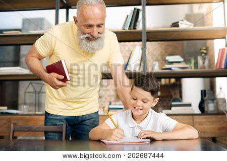 Always helpful. Pleasant smiling elderly man standing behind his grandson finishing his homework and looking into the notebook, checking the results of boys work