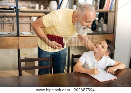 Help me out. Adorable little schoolboy sitting at the table and asking his grandfathers help with a home assignment while smiling at him charmingly