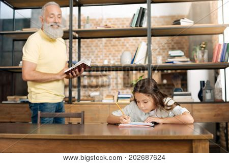 Help with English. Pleasant smiling elderly man dictating the list of words from the red notebook to his granddaughter learning English and practicing spelling