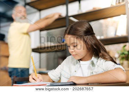 Hard-working student. Beautiful little girl sitting at the table and doing her home assignment while her grandfather taking something from the shelf in the background