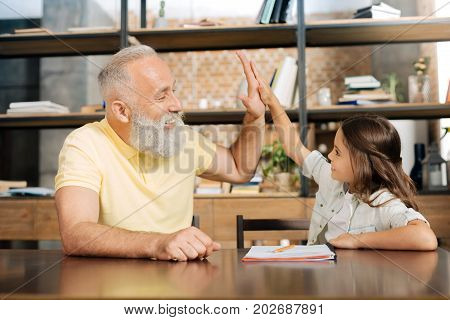 Well done. Adorable petite girl sitting at the table and giving her grandfather a high five, comparing her little palm with his