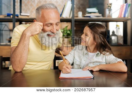 Genuine curiosity. Pleasant smiling senior man sitting next to his granddaughter and looking into her notebook with home assignment, checking it