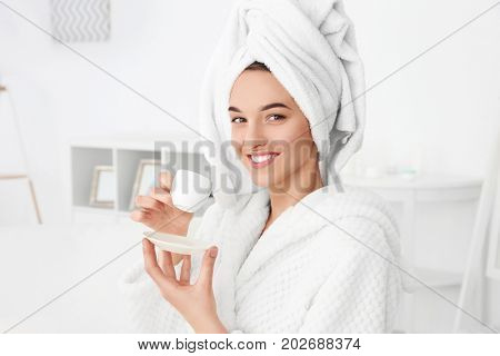 Beautiful young woman after shower in bathrobe with cup of coffee indoors