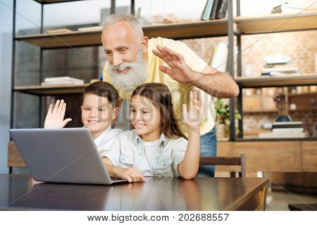 Nice to see you. Handsome senior man standing behind his little grandchildren sitting at the table and making a video call while all of them waving at the web camera