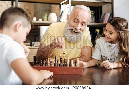 Interesting game. Adorable little girl sitting next to her grandfather and watching him play chess against her brother