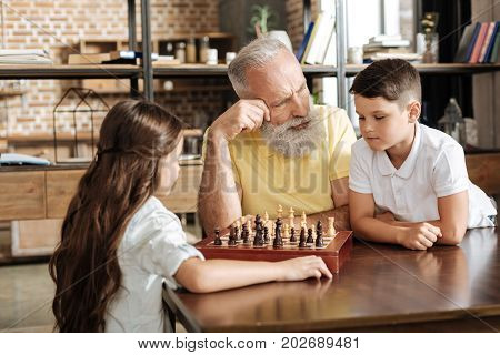 Crucial tip. Caring elderly man helping out his beloved grandson, giving him advice on next move in a chess game against his sister while the girl waiting for them patiently
