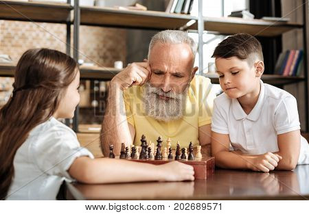 Pondering carefully. Pleasant senior man sitting next to his grandson and thinking about their next move in chess game against his charming little granddaughter