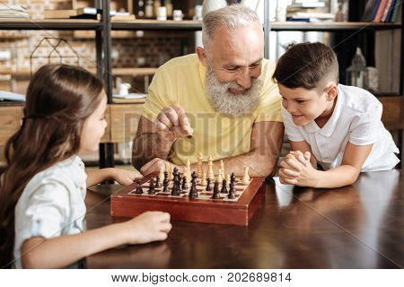 Best teacher. Caring smiling grandfather holding a pawn and explaining his beloved grandchildren the rules of chess while they listening to him attentively