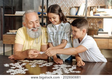 Best cooperation. Smiling happy senior man and his beloved grandchildren doing a jigsaw puzzle and uniting three pieces of puzzle together
