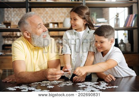 Enjoying themselves. Happy senior man assembling a jigsaw puzzle with his beloved grandchildren and laughing happily together with them while joining pieces
