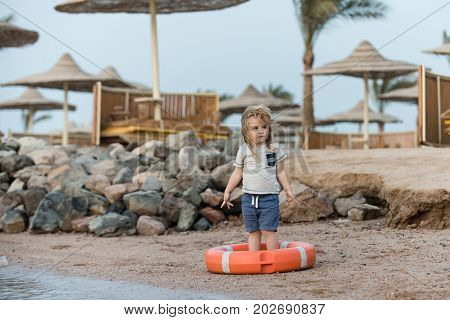 Safety on water on summer vacations. Happiness and expressive emotions. Boy child standing in life buoy. Small kid posing in orange life ring at beach. Baby care and childhood concept.