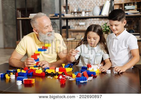 New favorite toy. Adorable pre-teen boy and girl standing near the table next to their grandfather and assembling a new construction set together with him