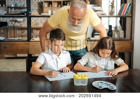 Favorite artists. Caring senior man standing behind his lovely grandchildren and watching them draw pictures using watercolors