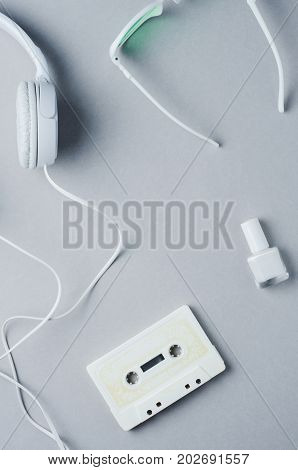 White Audio Cassette And Headphones On A Light Gray Background. Copy Space For Text Or Design