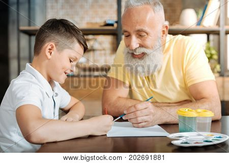 Absolute harmony. Sweet little boy sitting at the table next to his grandfather and painting with him a picture while smiling peacefully