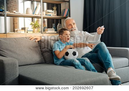 Make it louder. Pleasant senior man sitting on the couch next to his excited grandson and watching a football game with him while increasing the volume on TV set