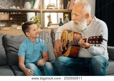 Inspiration vibes. Pleasant elderly man sitting on the couch next to his beloved grandson and playing guitar for him while the boy looking at him with admiration