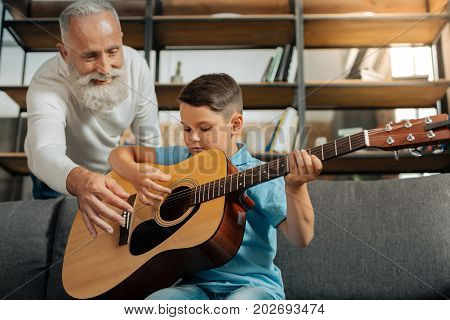 Practice makes perfect. Pleasant little boy holding a guitar and practicing how to strum chords while his beloved grandfather helping him