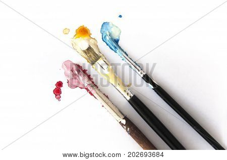 Three brushes in Cyan Magenta Yellow paint on white background. CMYK concept.