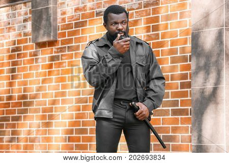 Security guard using portable radio outdoors