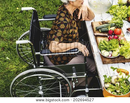Side view of handicap senior woman on wheelchair outdoors
