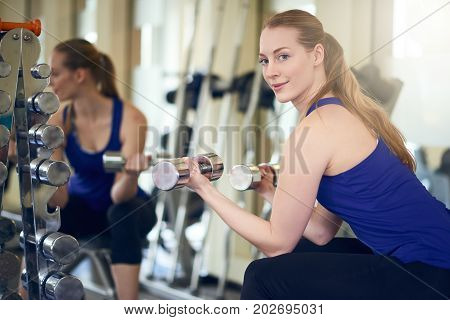 Fit healthy woman working out with weights in front of a large wall mirror in a gym turning to look over her shoulder at the camera as she holds two dumbbells