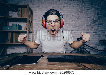 Young man playing game at home and streaming playthrough or walkthrough video. Stylish boy screaming because of fail. He is going to make revenge that's why he is holding his fists in attack position