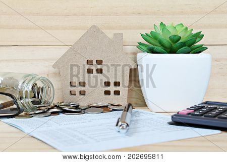 Business, finance, savings, property ladder or mortgage loan concept : Wood house mode, coins scattered from glass jar, calculator on saving account passbook or financial statement