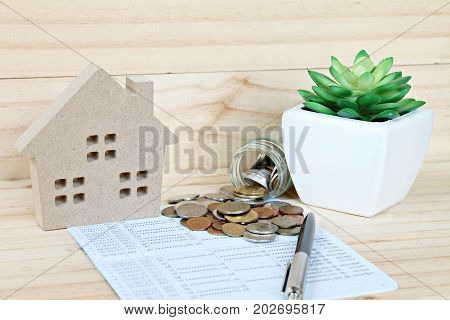 Business, finance, savings, property ladder or mortgage loan concept : Wood house mode, coins scattered from glass jar on saving account passbook or financial statement