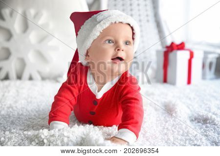 Cute little baby in Santa hat on soft fabric