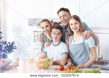 Home is where the family is. Four membered family embracing while standing at a kitchen island and grinning for the camera while preparing family dinner.