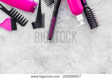 hairdresser work place with combs and brushes for styling and dyeing hair on stone desk background top view space for text