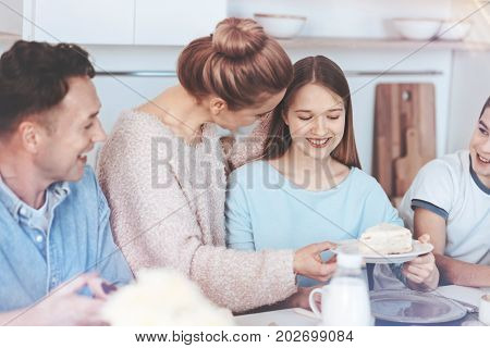 One slice for you honey. Selective focus on a loving mom standing next to her family while talking to her smiling daughter and giving her a plate with a slice of delicious cake on it.