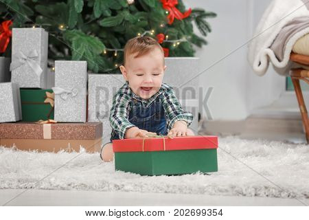Cute little baby with giftbox in room decorated for Christmas